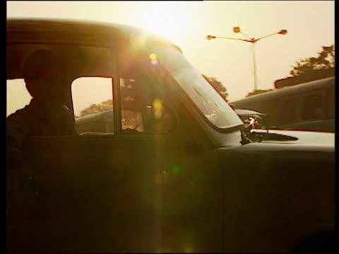 sunlight filtering through pollution and traffic on busy urban road at dusk mumbai - mumbai stock videos & royalty-free footage