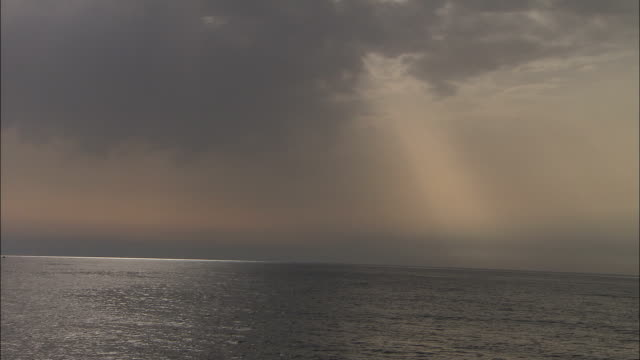 sunlight filters through gray clouds above the mediterranean sea. available in hd. - 光点の映像素材/bロール