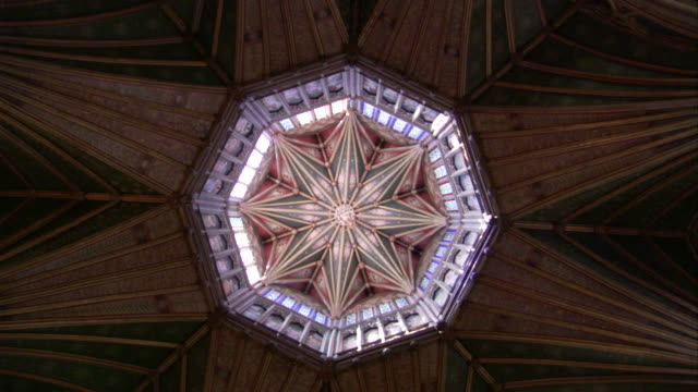 sunlight floods in through stained glass windows on the walls and in the ceiling of ely cathedral. available in hd. - octagon stock videos & royalty-free footage