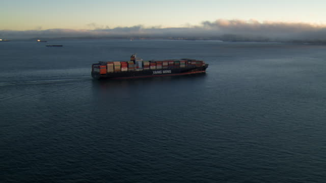Sunlight gleams on the water as a loaded container ship moves toward the Oakland Bay Bridge.