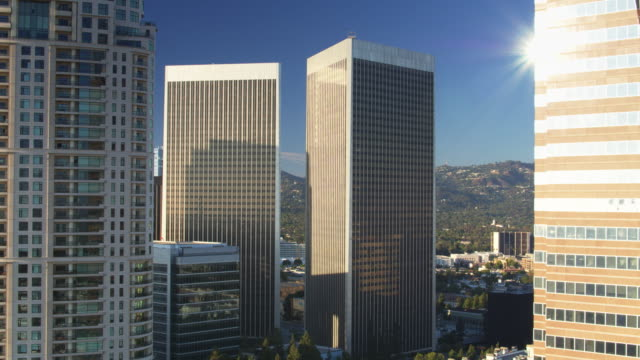 sunlight glinting on skyscrapers in century city, los angeles - drone shot - century city stock videos & royalty-free footage