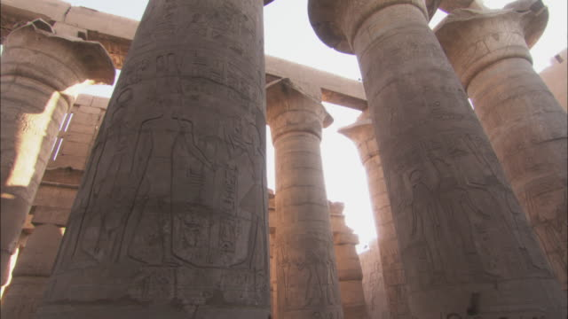 sunlight glows between carved pillars of the karnak temple in egypt. - temples of karnak stock videos and b-roll footage