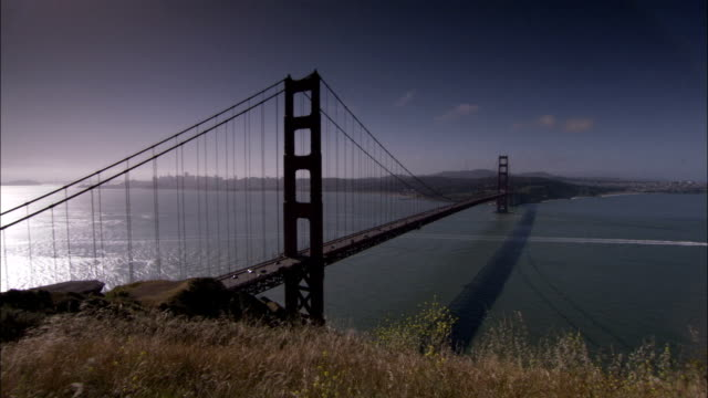 sunlight glows on san francisco bay and the golden gate bridge. available in hd. - golden gate bridge stock-videos und b-roll-filmmaterial
