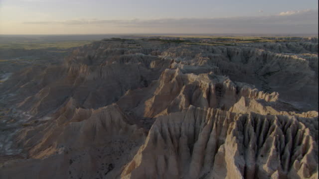 sunlight hits the towering rock formations in badlands national park. available in hd. - badlands national park video stock e b–roll