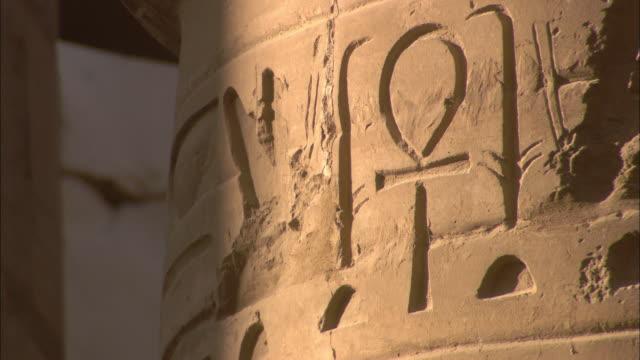 Sunlight illuminates an Ankh and other Egyptian symbols on the walls of Karnak Temple.