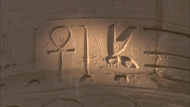 sunlight illuminates egyptian hieroglyphic symbols in the karnak temple. - temples of karnak stock videos & royalty-free footage
