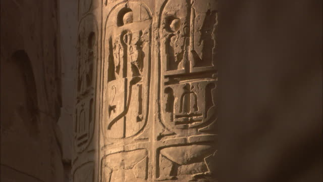 Sunlight illuminates Egyptian hieroglyphs on the walls of Karnak Temple.
