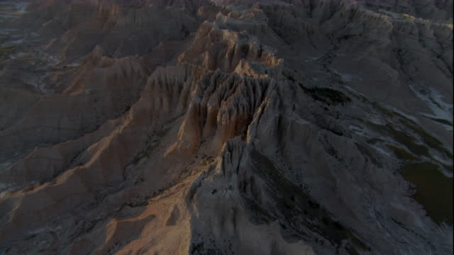 sunlight illuminates eroded rock formations in badlands national park. available in hd. - badlands national park video stock e b–roll