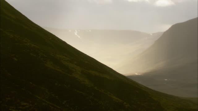 Sunlight illuminates rain in valley, Cairngorms, Scotland