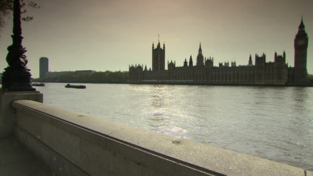 sunlight on river thames and houses of parliament - flussufer stock-videos und b-roll-filmmaterial