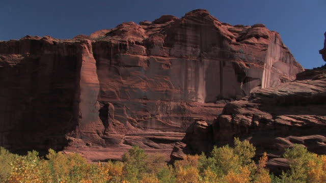 ms sunlight on rock wall with trees below/ canyon de chelly national monument, arizona - canyon de chelly stock videos & royalty-free footage