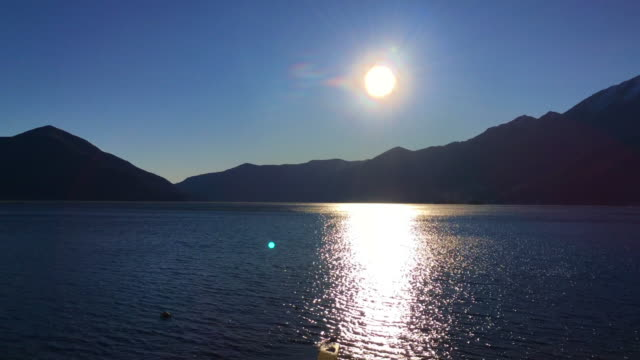 sunlight over alpine lake with mountain in a sunny day - viewpoint stock videos & royalty-free footage