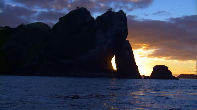 vídeos y material grabado en eventos de stock de sunlight peeks out between a massive rock formation surrounded by water. - provincia occidental del cabo