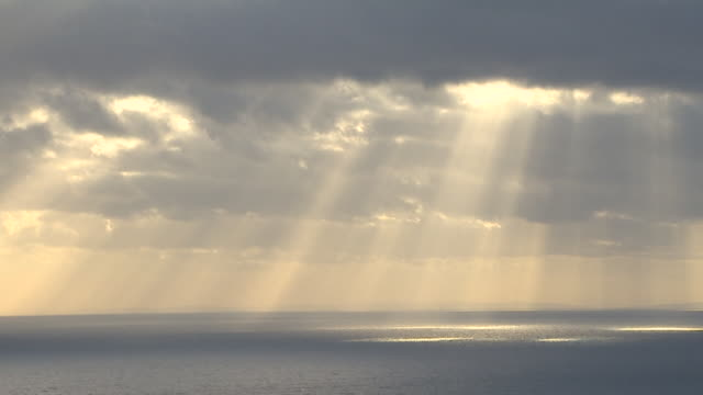 sunlight rays shining through clouds onto shimmering still sea - sky only stock videos & royalty-free footage
