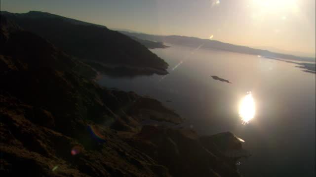 sunlight reflects off lake mead near a mountainous shore. - lake mead video stock e b–roll