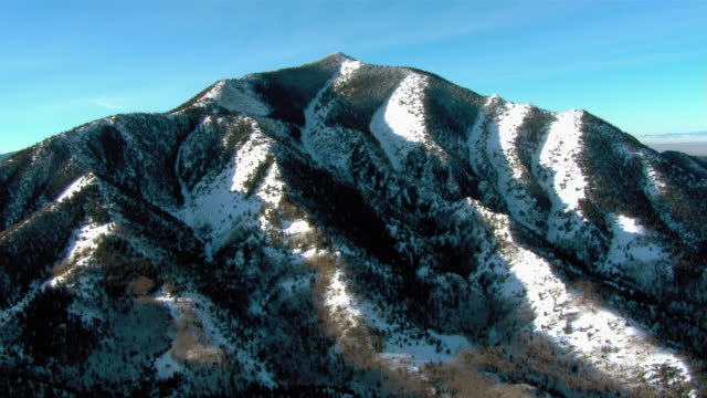 Sunlight reflects on snow covered mountain slopes.