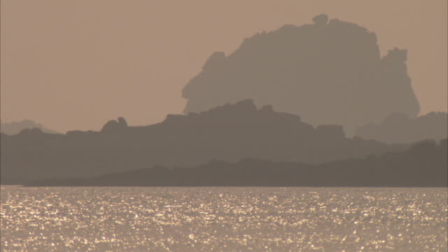 sunlight shimmers near a hazy coast. available in hd. - isles of scilly stock videos & royalty-free footage