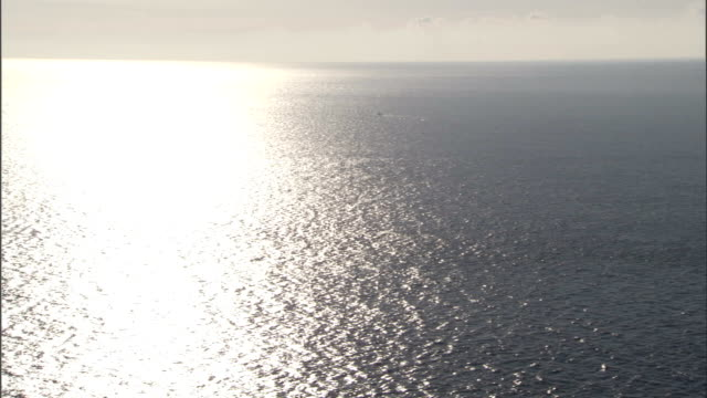 Sunlight shimmers on the surface of the Atlantic Ocean as a cargo ship sails toward the Mediterranean Sea. Available in HD.