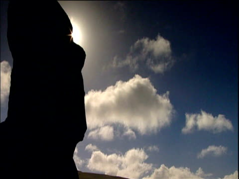 sunlight shines behind moai statues of easter island blue sky and clouds in background - polynesian culture stock videos & royalty-free footage