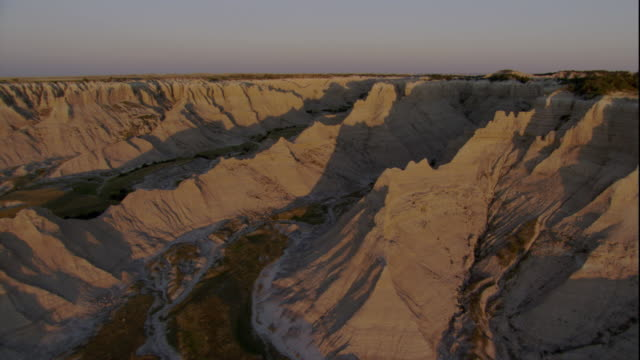 sunlight shines on eroded mountain ridges in badlands national park. available in hd. - badlands national park video stock e b–roll