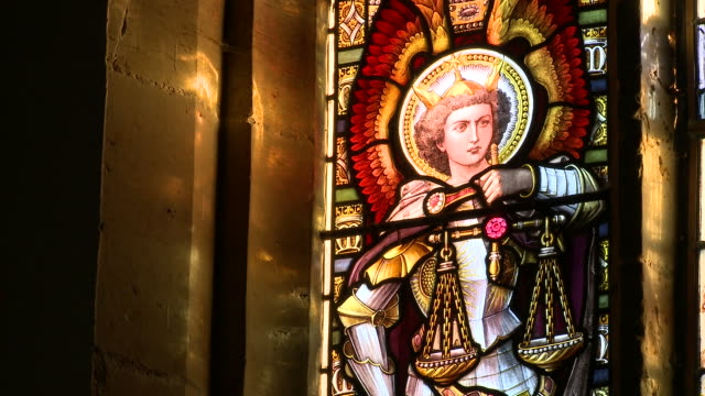 Sunlight shines through a beautiful stained glass window in a church.