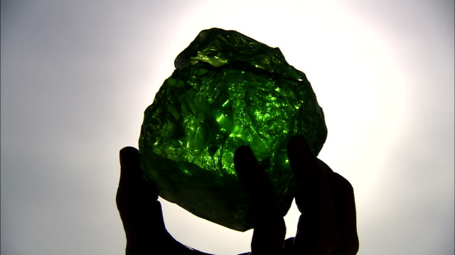 sunlight shines through a large piece of green desert glass. - gemstone stock videos & royalty-free footage
