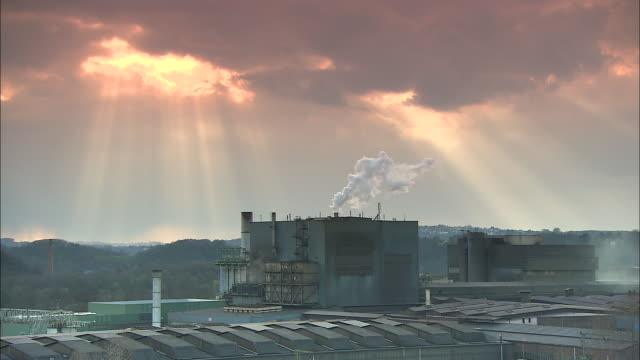 sunlight shines through clouds and down on an industrial site. - north rhine westphalia stock videos & royalty-free footage