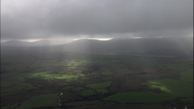 vídeos de stock e filmes b-roll de sunlight shines through clouds over the green farmlands of wales. - país de gales