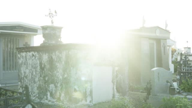 sunlight shines through monuments in saint paul marine cemetery - saint paul stock-videos und b-roll-filmmaterial