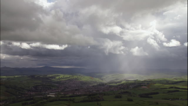 vídeos de stock, filmes e b-roll de sunlight shines through storm clouds over the green countryside of scotland. - escócia