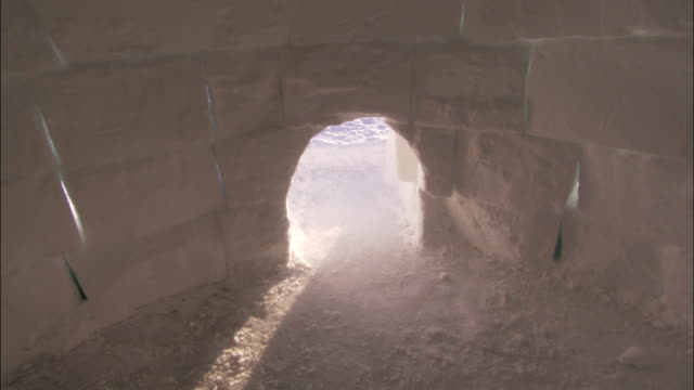 sunlight shines through the arched entrance of an igloo. available in hd. - igloo stock videos & royalty-free footage