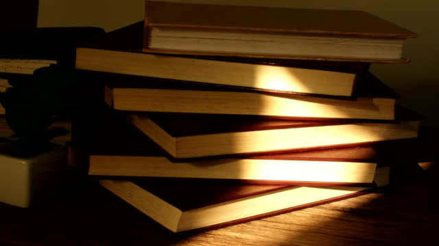 sunlight shining on the stack of books - libro in brossura video stock e b–roll