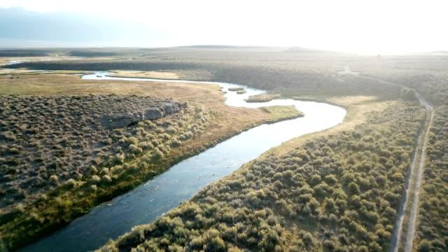 vídeos y material grabado en eventos de stock de luz del sol brillando sobre río y llanura cubierta de hierba - oasis desierto