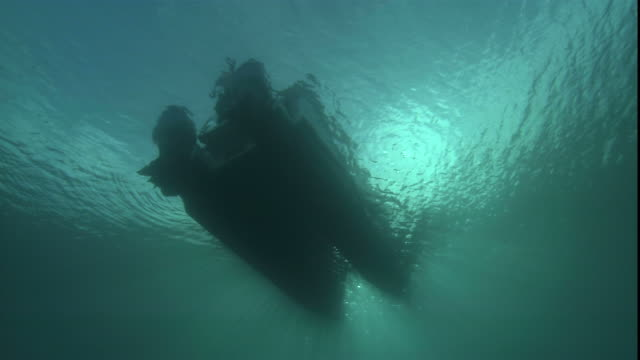 sunlight silhouettes a boat floating on the ocean's surface. - galleggiare sull'acqua video stock e b–roll