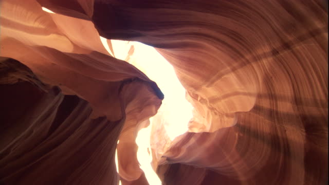 Sunlight streams in through the narrow opening of a slot canyon, Utah. Available in HD.
