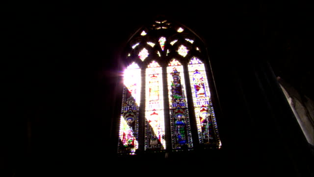 Sunlight streams through a stained glass window in the Ely Cathedral. Available in HD.