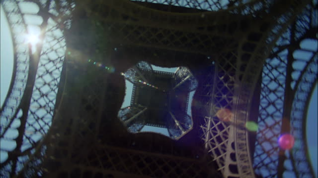 sunlight streams through the beams of the eiffel tower. - dizzy stock videos & royalty-free footage