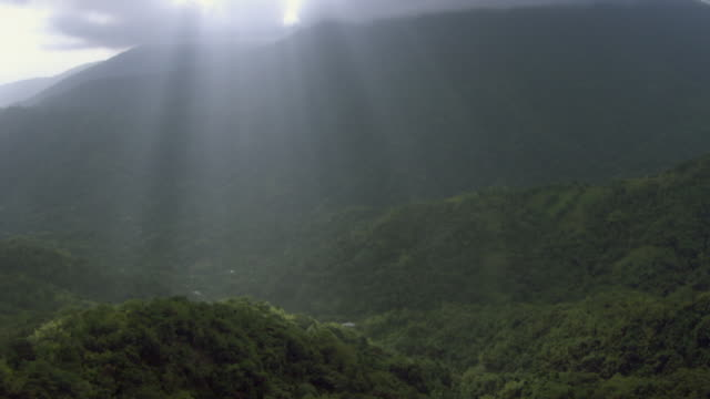 Sunlight streams through the clouds over the Blue Mountains in Jamaica.