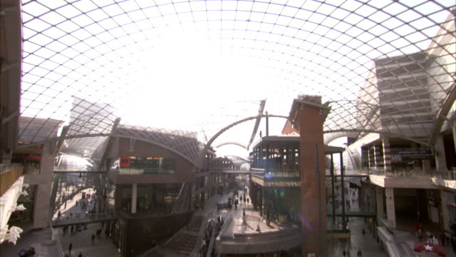 sunlight streams through the glass roof of cabot circus shopping centre in bristol. available in hd. - atrio cuore video stock e b–roll