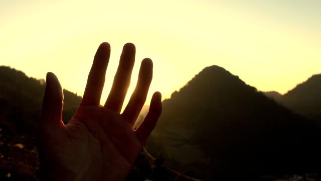 vidéos et rushes de sunlight through finger at sunset - un seul homme d'âge moyen