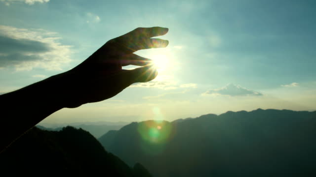 vidéos et rushes de rayonnement solaire à travers de la main - attraper