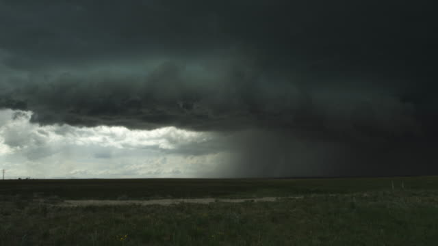 Sunlight under dark shelf cloud at left as heavy rain falls on prairie at right, time lapse