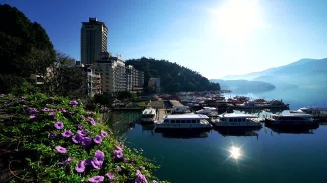 sunlight's reflection on sun moon lake in shuishe pier, taiwan - sun moon lake stock videos and b-roll footage