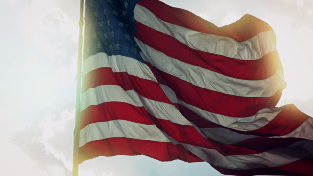 sunlit american flag blowing in wind - partito repubblicano degli usa video stock e b–roll