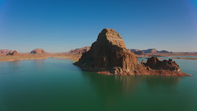aerial sunlit butte rising above lake powell, usa - butte rocky outcrop stock videos & royalty-free footage