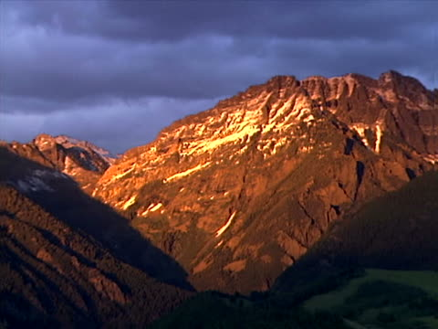 a sunlit mountain under dark skies - artbeats stock videos & royalty-free footage
