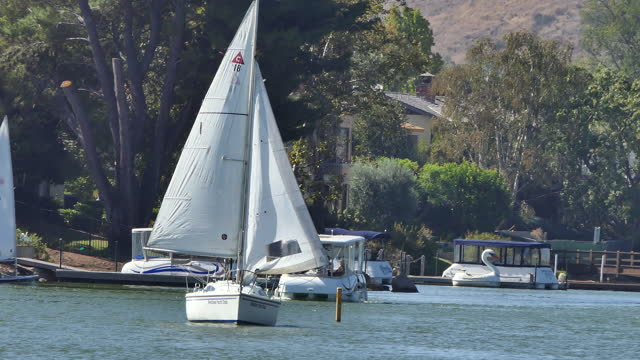 sunny afternoon on a small southern california lake with a sailboat sailing to camera a pontoon boat and a dinghy in the background westlake yacht... - westlake village california stock videos & royalty-free footage