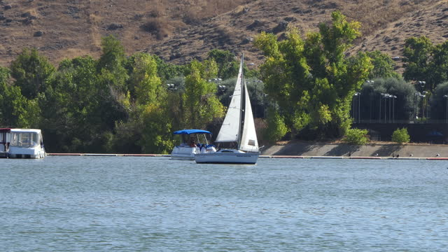 sunny afternoon on a small southern california lake with people on two dinghies a sailboat and a pontoon boat sale past camera westlake village a... - westlake village california stock videos & royalty-free footage