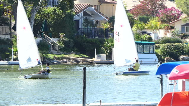 sunny afternoon on a small southern california lake with people on two dinghies sale past camera a pontoon boat tied to a dock in the background... - westlake village california stock videos & royalty-free footage