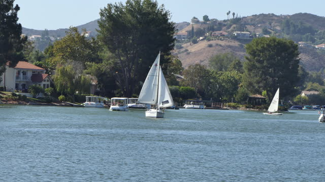 sunny afternoon on a small southern california lake zoom out from a sailboat sailing to camera a pontoon boat and a dinghy in the background westlake... - westlake village california stock videos & royalty-free footage